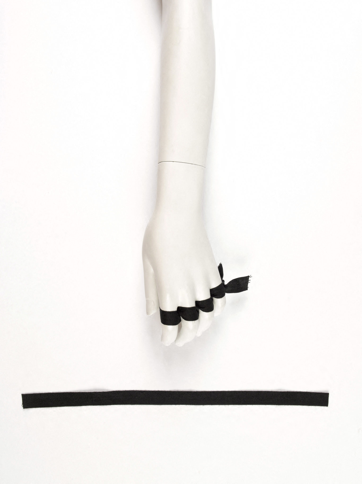 Image de défilé de la collection automne-hiver 1991-1992 accompagnée d'un sachet contenant deux rubans de couleur noire, Martin Margiela